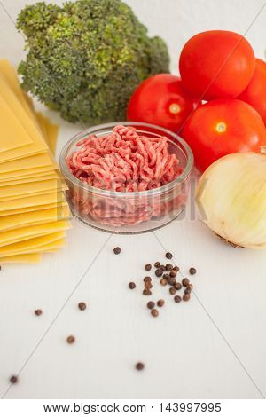 Set of ingredients for traditional italian lasagna on the table. Pasta, tomatoes, fresh ground meat, parmesan, onion, broccoli.