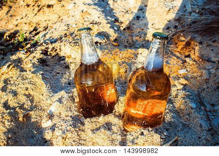 Two fresh bottles of beer in the sawdust in the sun.