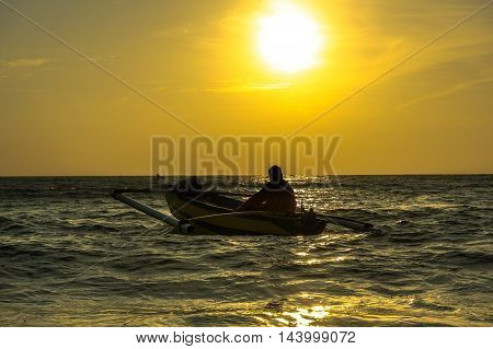 Beautiful sunset in Labuan island with the silhouette of a fisherman with traditional fishing boat at Manikar beach,Labuan Pearl of Borneo.