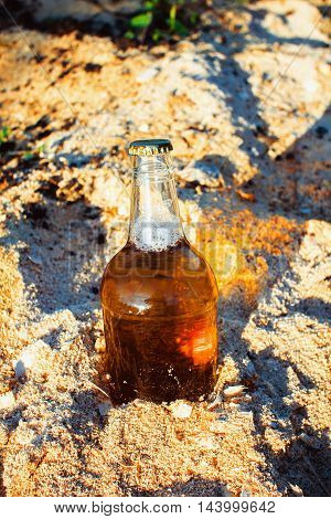 Fresh bottle of beer in the sawdust in the sun.