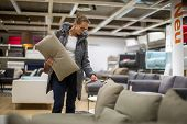 Pretty, young woman choosing the right furniture for her apartment in a modern home furnishings stor poster