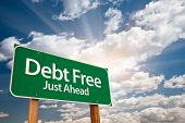 stock photo of debt free  - Debt Free Green Road Sign with Dramatic Clouds - JPG