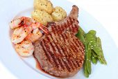 Rib-eye steak with shrimps and vegetables.