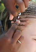 stock photo of cornrow  - native women braiding young girls hair with beads and cornrows - JPG