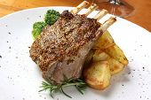 Rack of lamb with seeded mustard, served with roasted potatoes and rosemary.