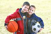 stock photo of children playing  - Two young boys holding sports balls under their arms