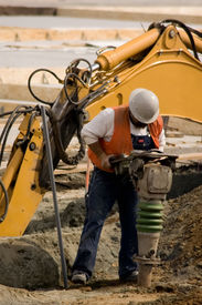 pic of blue-collar-worker  - A construction worker using a large soil tamping machine - JPG