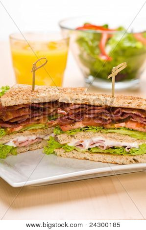 Two Sandwich On Plate With Juice And Salad Bowl