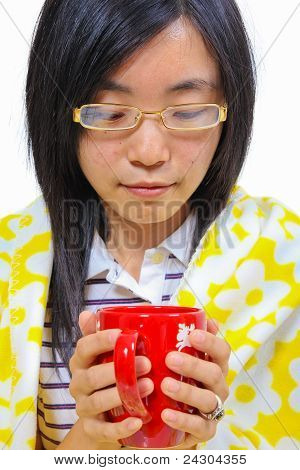 Chinese Woman Sitting Under A Blanket With A Cup Of Tea