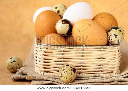 Group of brown and white hen's eggs  in a wicker basket