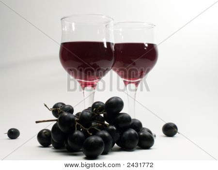 Two Bocals Of Red Wine And Bunch Of Grapes