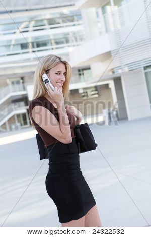 A pretty blonde business woman on the phone at the office building