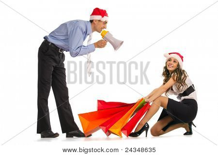 Manager shouting into the megaphone about christmas sale and stylish young woman pulling shopping bags over white background