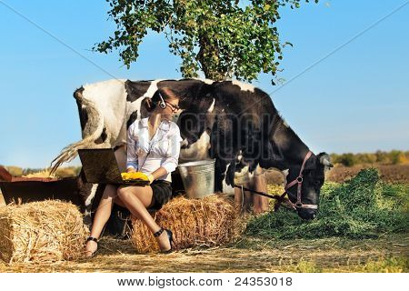 Business woman with laptop milking cow on farm