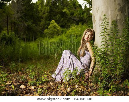 A beautiful young lady sitting in a tree in the forest