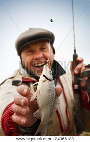 Happy mature fisherman with fresh caught crucian (Carassius of family Cyprinidae) on clear sky background