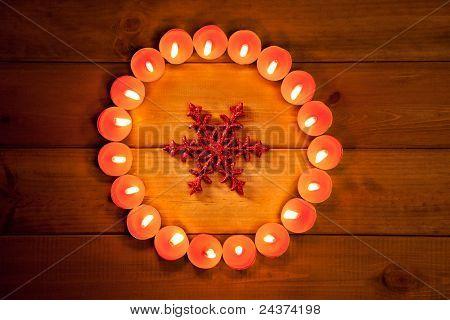círculo de velas de Navidad sobre símbolo de copo de nieve de madera y rojo