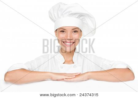 Chef or baker woman showing blank empty billboard sign. Beautiful smiling happy chef leaning on placard banner with copy space for menu or other text.