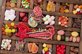 Colorful sweets box. Lollipops, macaroons, marshmallow, marmalade and candies. Top view poster