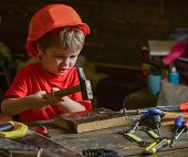 Child In Helmet Cute Playing As Builder Or Repairer, Repairing Or Handcrafting. Toddler On Busy Face poster