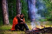 Young Couple Roast Sausages On Stick On Bonfire In Forest. Couple In Love At Picnic In Forest, Trees poster
