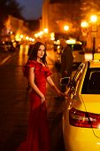 Luxury Woman In Evening Dress At Night City Go To Prom On Taxi. Luxury Woman In Red Dress Wait Taxi poster