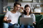 Millennial Couple Annoyed By Stuck Laptop Or Online News Sitting Together On Sofa, Frustrated Young  poster