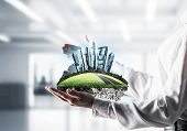Cropped Image Of Business Woman In Shirt Keeping Green Island With Metropolis City In Her Hands With poster