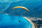 Paragliding In The Sky. Paraglider Tandem Flying Over The Sea With Blue Water, Beach And Mountains I poster