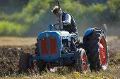 foto of chug  - Old Tractor ploughing field in rural countryside