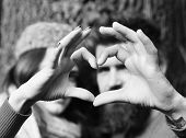 Couple In Love Shows Heart Sign With Fingers. Lovers. Girl In Pink Hat And Bearded Guy Or Happy Love poster