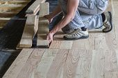 Close Up Of Professional Carpenter Installing Natural Wooden New Planks On Cement Floor In Empty Unf poster