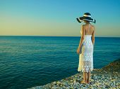 stock photo of beach hat  - Elegant young woman in a hat standing on beach - JPG