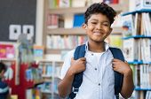 Portrait of smiling hispanic boy looking at camera. Young elementary schoolboy carrying backpack and poster