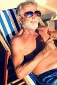 Senior man chilling and drinking wine on deck chair poster