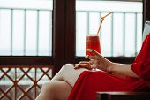Close Up Of Woman In Red Dress With Red Cocktail With Orange Straw In Hands. Beautiful Girl In Red D poster