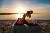 Silhouette Woman On The Beach At Sunset Doing Yoga Asana. Morning Natural Stretch Warm-up Training poster