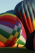 stock photo of underdog  - A worker assists as Hot Air Balloons get ready to take off - JPG