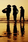 pic of fisherwomen  - Three fisherwomen on the beach in Vietnam at sunset - JPG
