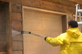 stock photo of pressure-wash  - a man pressure washing a wood sided garage - JPG
