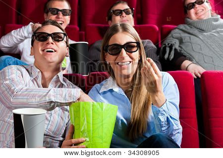 Couple in cinema theater watching a movie in 3D with glasses and popcorn