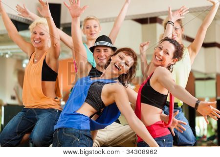 young people dancing in a studio or gym doing sports or practicing a dance number