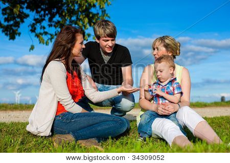 Family - Grandmother, mother, father and child sitting and playing in garden