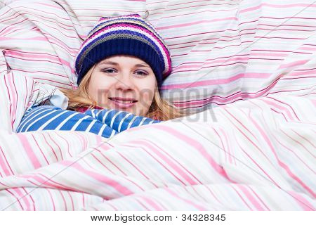 Smiling Woman In Winter Hat Wrapped In Duvet
