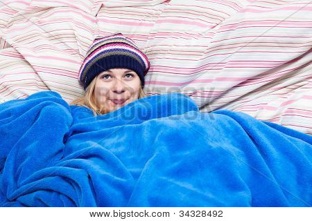 Cute Woman In Winter Hat Wrapped In Duvet