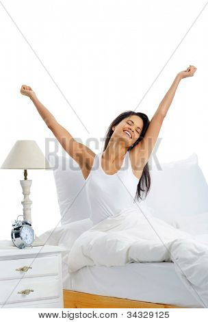 Joy cheerful happy woman waking up with a smile in bed and stretching her arms up