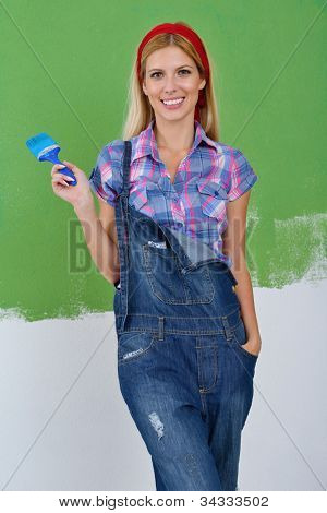 happy smiling woman painting interior white  wall in blue and green color of new house