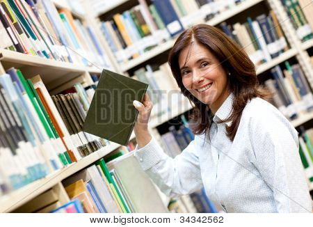 Librarian placing a book in the bookshelf and smiling