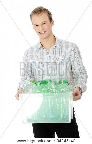 Young, handsome, smiling man holding white box full of plastic, green bottles. Blond man wearing plaid bright shirt and black trousers. Isolated on the white background.