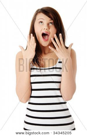 Surprised young woman screaming in excitement and showing hands and all fingers. Long-hair brunette with eyes upward and open mouth wearing striped, black and white top. Isolated on white background.